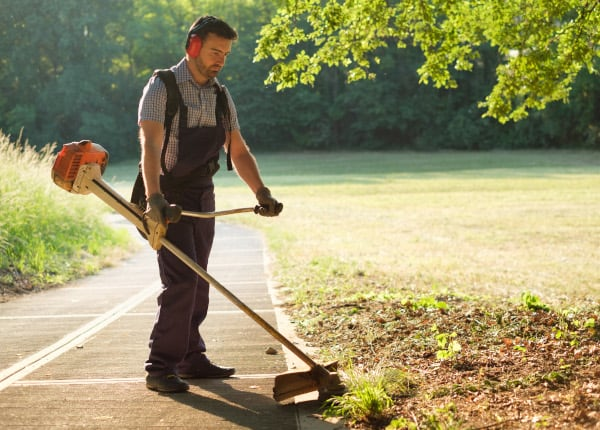 Professional gardener using a lawn edger in the home garden